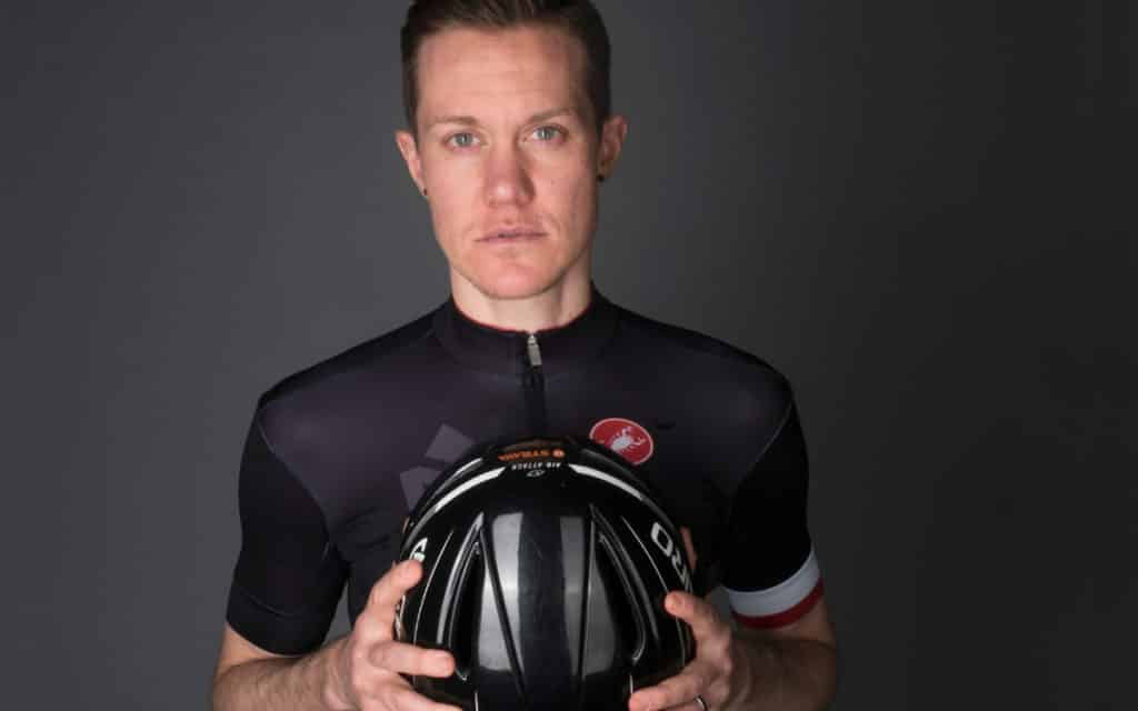 Chris Mosier holding bicycle helmet in a black background