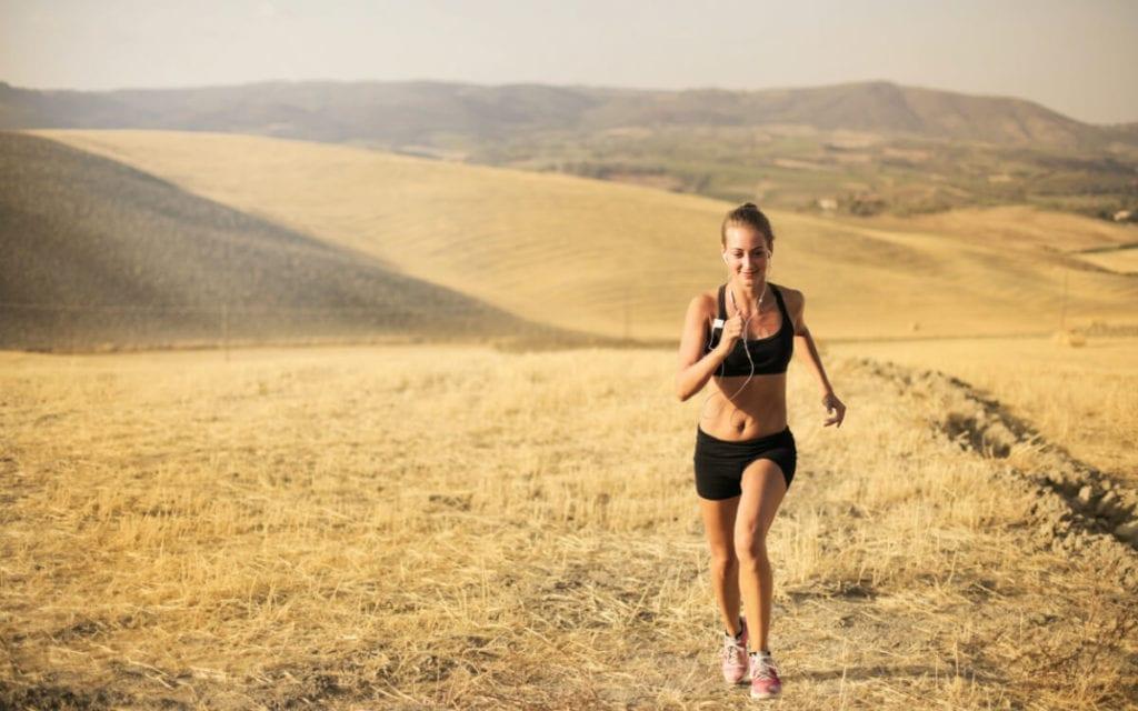 A woman running on a dried grass field